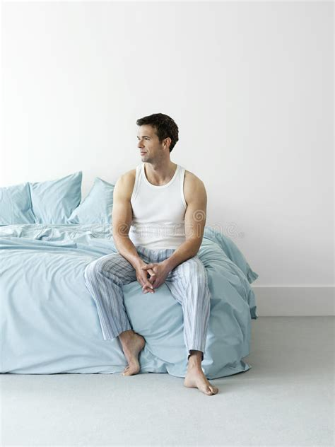 sitting in bed thoughtful man in nightwear sitting in bed stock photos