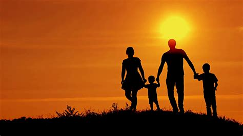 family background silhouettes of happy family running on a sunset background
