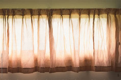 closed curtains sunlight through closed curtains by kristin duvall window light stocksy united