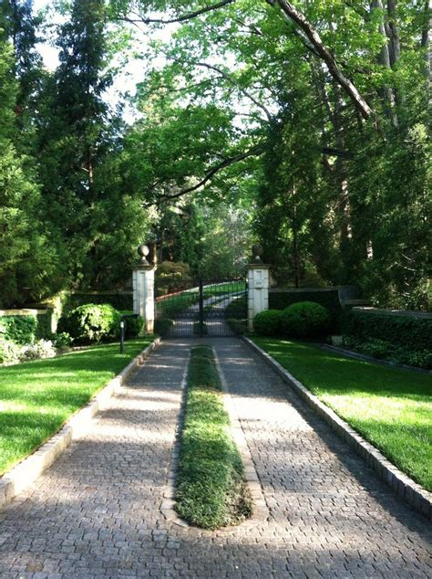 lovely entrance and paver driveway with grassy strip