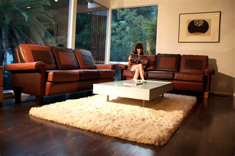 living room with brown furniture white fur rug with glass top living room table and brown leather sofa with arms for small