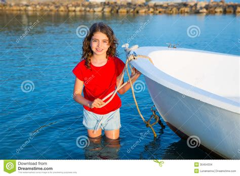 girl on bow of boat kid girl pretending to be sailor in boat bow at formentera