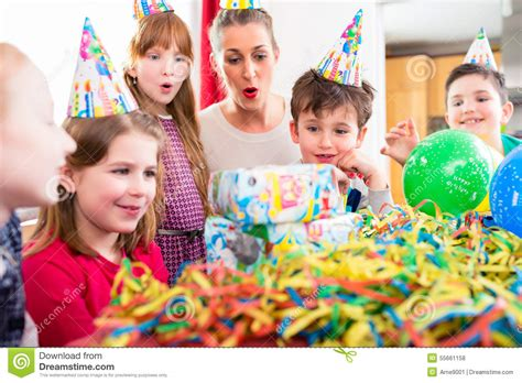 child unwrapping birthday gift with friends stock photo