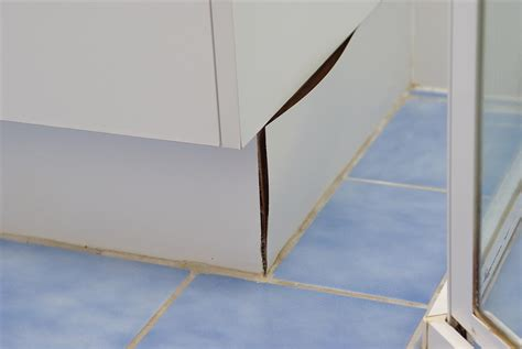 water under tiles in bathroom should you tile under bathroom vanities or kitchen cabinets renovate australia