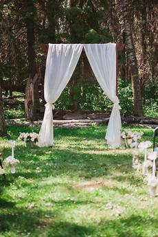 white curtain outdoor wedding arch