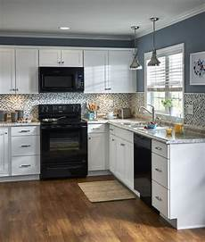 Kitchen Cabinet Colors With Black Appliances by White Cabinetry And A Mosaic Tile Backsplash Contrast With