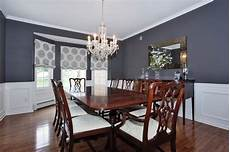 traditional dining room with chair rail bay window crown molding wainscoting chandelier