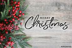 merry christmas text with christmas evergreen branches and berries in corner over rustic wooden