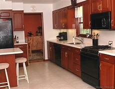 Kitchen Cabinet Colors With Black Appliances by Traditional Medium Wood Cherry Kitchen Cabinets With Black
