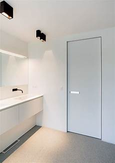 invisible doors turn a modern home into an artistic feat of white interior door with invisible door frame and a built