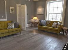 grey wood laminate flooring in living room with yellow