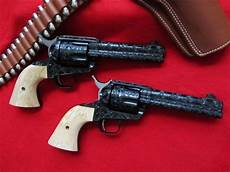 two genuine colt sixguns in 45 lc master blued with fitted ivory grips and full scroll