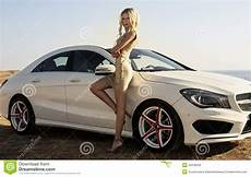 With Blond Hair Posing Beside A Luxury Auto Stock