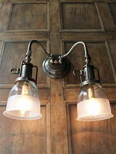 brass double arm wall light with half frosted glass shades