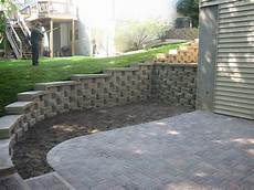 i block pavers for outdoors retaining wall with caps and a paver patio installed in