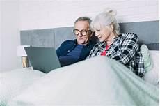 anziani a letto coppia di anziani a letto con il portatile scaricare