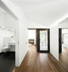 white walls and in floor storage make this creative house design white walls timber floor home grey decks