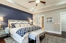master bedroom with light gray walls and dark blue accent wall behind tufted bed interior