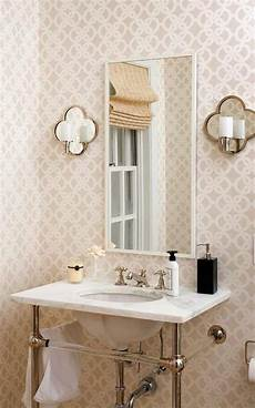 powder room with wallpaper and mirrored wall sconces the