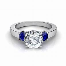 three stone round brilliant engagement ring with blue sapphires
