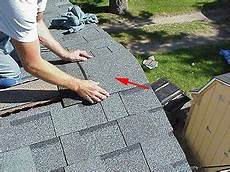 installing ridge cap shingles at ends of roof peak before