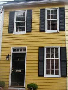dark mustard yellow darker than this white trim black doors shutters warm creamy gray and