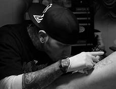 tattoo artist at work in black and white photograph by