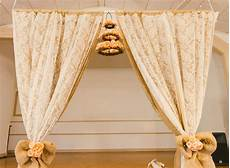 diy wedding arch lace curtains from thrift store and layers of cheap burlap secured to