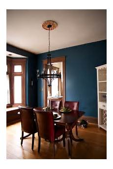 dark teal wall paint and unpainted wooden trim for the dining room dining room blue dining