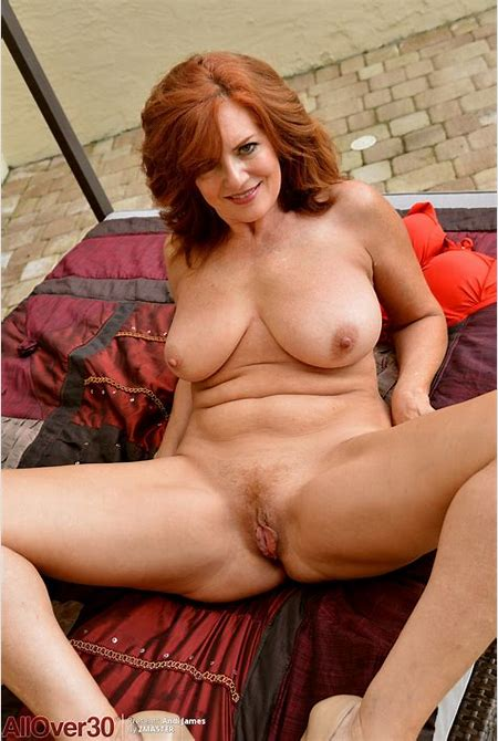 Mature redhead Andi James cups her natural tits while ...
