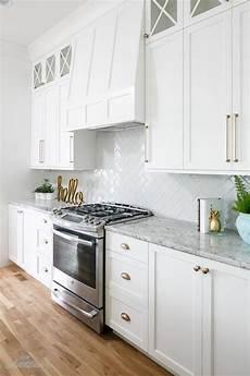 a stainless steel oven range sits against white herringbone backsplash tiles beneath a white
