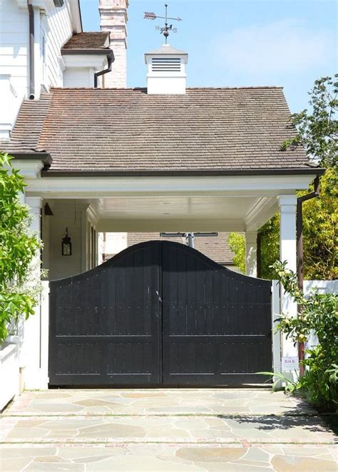 Black Curvy Entrance Gate Designs With Stone Driveway For