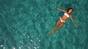 Aerial - Young woman floating in crystal clear water Stock ...