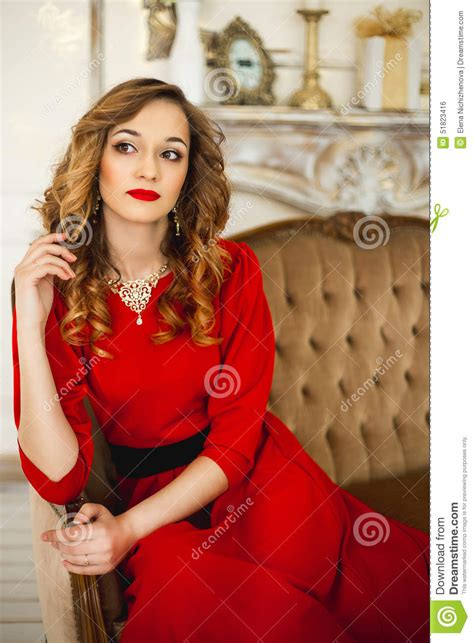 The Girl In A Red Dress With Gold Costume Jewelry Stock Photo - Image 51823416