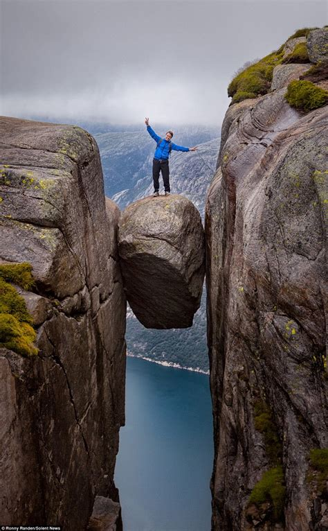 Daredevil Tourists Pose On Kjeragbolten Boulder Wedged In