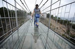 Tourists walk China's new glass-bottom walkway suspended ...