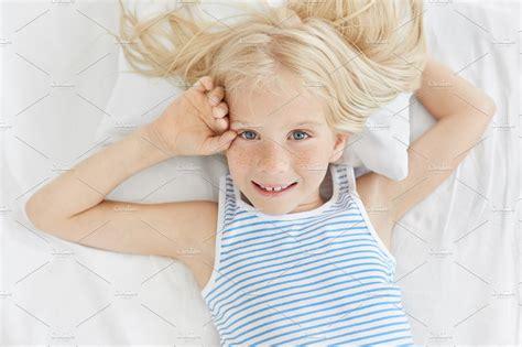 freckled blue eyed girl  blonde hair wearing striped