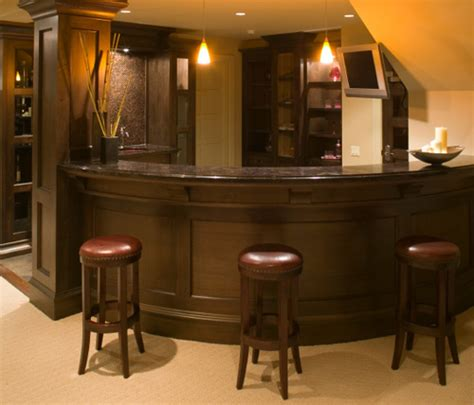 curved home bar tucks into basement stairwell