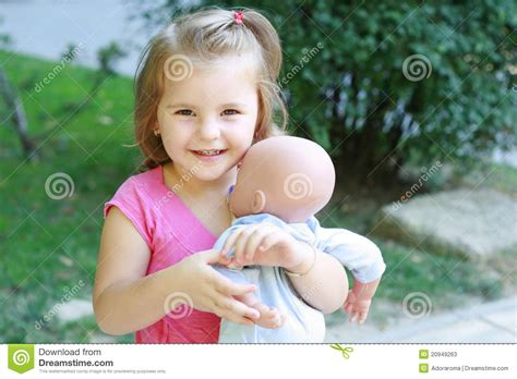 Little Girl Playing With A Baby Doll Stock Photos