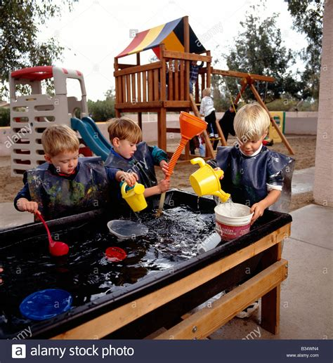 children at a water table in an arizona 777 | young children playing at a water table game in an arizona preschool B34WN4