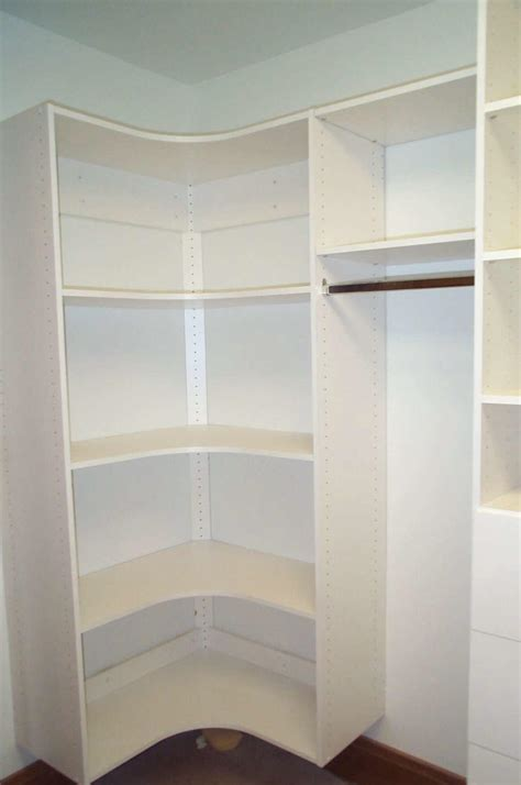 white closet with l shaped white wooden shelves and brown
