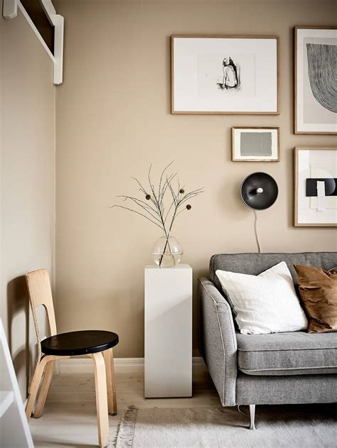 Gorgeous living room designed with a bull head wall decor in between floating wooden shelves. Small studio with beige walls - COCO LAPINE DESIGNCOCO LAPINE DESIGN