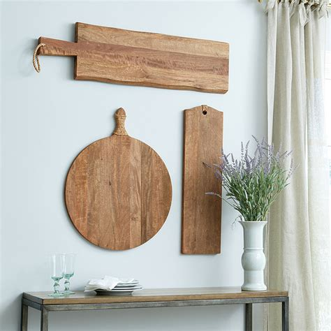 You can use one or a few cutting boards clustered together against the wall. Cutting Board Wall Decor