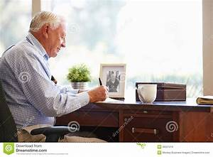 Senior Man Writing Memoirs In Book Sitting At Desk Stock ...