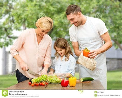 happy family cooking vegetable salad for dinner stock