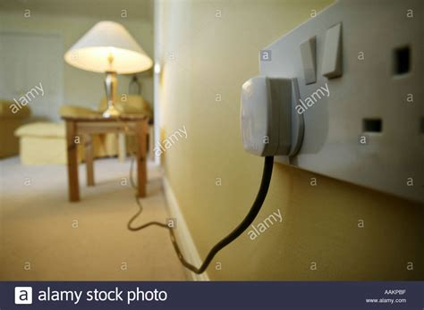 a table l plugged into a wall socket in the uk stock