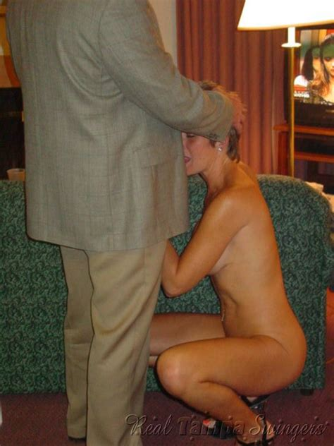 The Naked Wife Is Sitting On Her Knees And Taking The Guy S Pecker In With Her Lips