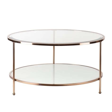A table has a base of 2 crossed panels. Southern Enterprises Risa Round Glass Top Coffee Table in Gold - CK0430