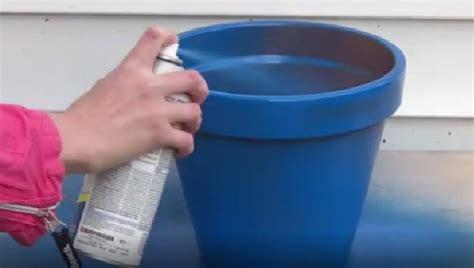 elle peint en bleu  pots en terre cuite puis les sa