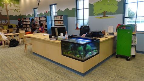 Custom Home Interiors - t2 design custom circulation desk with fish tank library interiors of texas